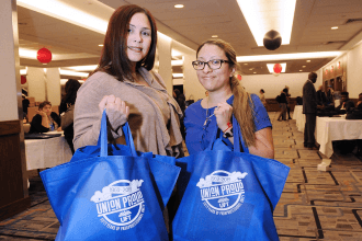 Two women holding up union swag bags