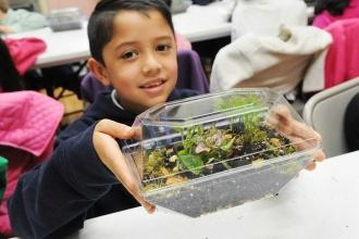 A student displays his completed terrarium.