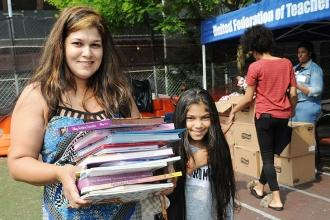 Samantha Persaud carries an armful of books for her daughter, who attends PS 123