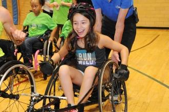 A student tries out a racing wheelchair.