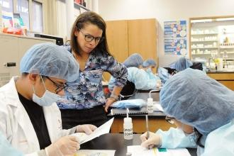 Teacher Leonela Garcia checks as a student team prepares a doctor's prescription