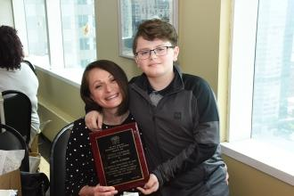 Child poses with arm around counselor holding award