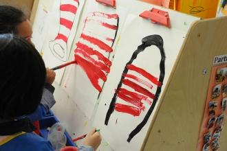 Students show their love for Dr. Seuss' stories by painting the signature hat wo