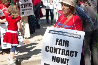 "Woman wearing red with sign, ""Fair contract now"""