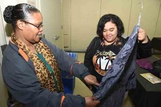 Shirley Taft (left), a social worker at IS 404 in the Bronx, examines a dress wi