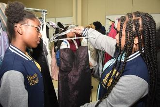 An 8th-grade student from IS 217 in the Bronx checks out a dress with her teache