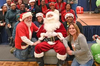 Volunteers join the Santas for a Christmas portrait.
