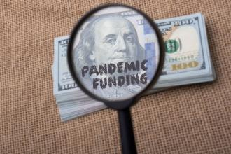 "Clipart image of a magnifying glass showing the words ""pandemic funding"" on a dollar bill"