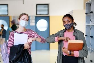Two teachers wearing masks bump elbows instead of shaking hands.