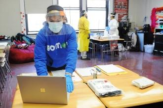 Student with facial shield and mask at computer