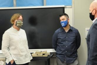 A woman turns to talk to two men in a classroom. All are wearing masks.