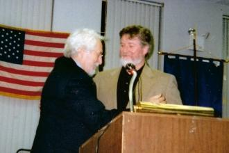 Two men at a podium and one is receiving an award