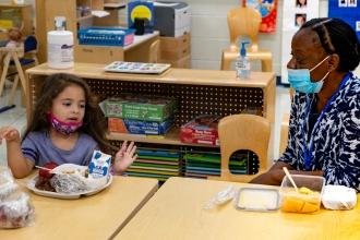 Paraprofessional eats breakfast with pre-K student