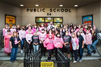 A group photo of staff at a public school in Staten Island. Most are wearing breast cancer awareness masks.