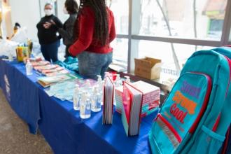 Volunteers stand ready behind a table with books, a backpack and hand sanitizer