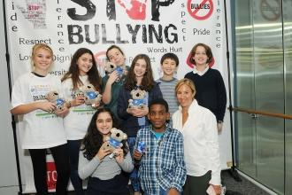 Group of students with teacher in front of sign that says STOP BULLYING