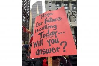 Woman holding Sign: Mayor our future is calling today.. will you answer