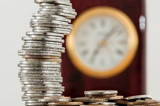 Stack coins in front of an out of focus clock