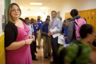 UFT master teacher in pink dress standing in crowded school hallway