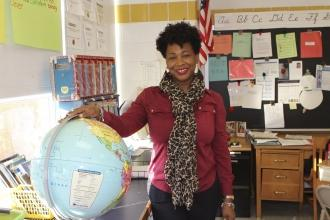 UFT model teacher standing in classroom with one hand on globe