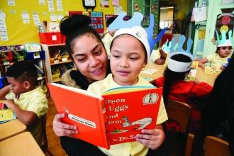 Parent and student in classroom reading Dr. Seuss book