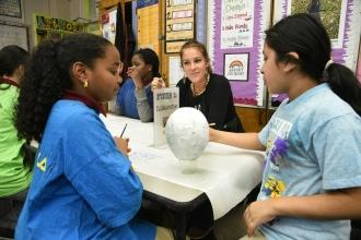 Two girls in foreground painting white orb, UFT teacher in background - professional development