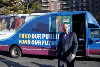 Man walks in front of bus that reads Fund Our Public Schools