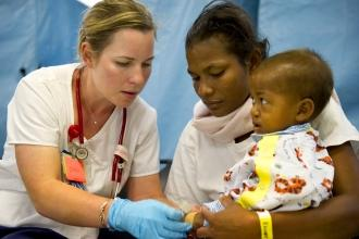 Woman wearing stethoscope touches young child held by mother
