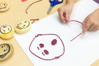 A student wearing a mask participates in art class