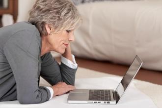 Mature woman laying on the floor looking at her laptop