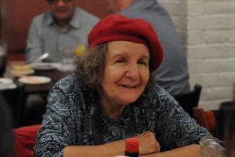 Mature woman with red hat seated at table