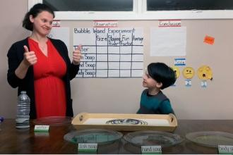 Woman and child in front of a chart that says Bubble Wand Experiment