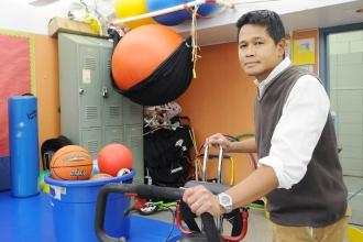 A man stands with an adaptive exercise device in a room full of exercise balls and gym equipment