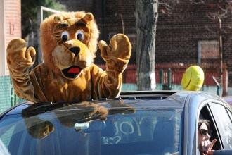 East Elmhurst Community School mascot Lucy the Lion (teacher Caitlin Antompietri) greets students along the parade route