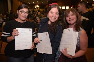 Three smiling women displaying certificates, representing UFT teacher certification
