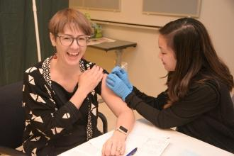 Smiling woman receiving flu shot through UFT health benefits