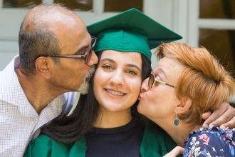 Teenager wearing graduation cap being kissed by two adults