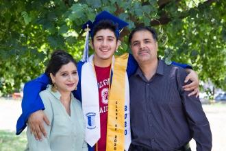Teenager wearing graduation cap with his arm around two adults