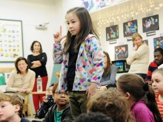 A 2nd-grader introduces herself with her name sign.