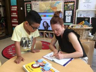 "Actress Julianne Moore signs a copy of her book ""Freckleface Strawberry"" in a 20"