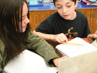 Two students discuss what they have learned about labor leader Samuel Gompers an