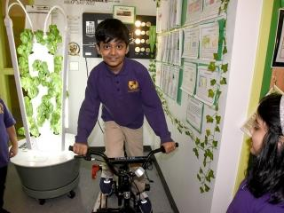 A student uses pedal power to convert human energy into usable energy to power s