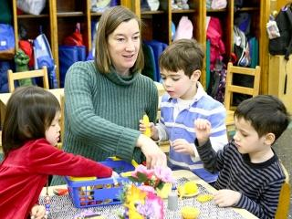 Literacy teacher Noelle O'Reilly helps three 4-year-olds set the table for dinne