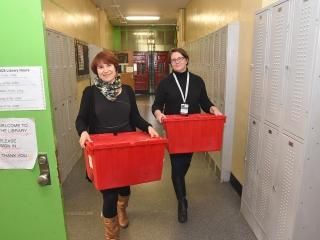 Librarians Susan Westover (left) and Amanda Clarke deliver the big, red bins to