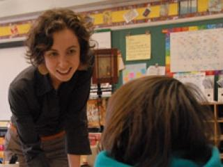Teacher interacting with student with chalkboard in the background