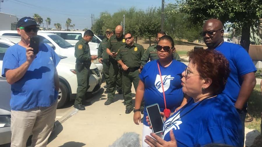 AFT representatives wearing blue AFT shirts with border agents in uniform