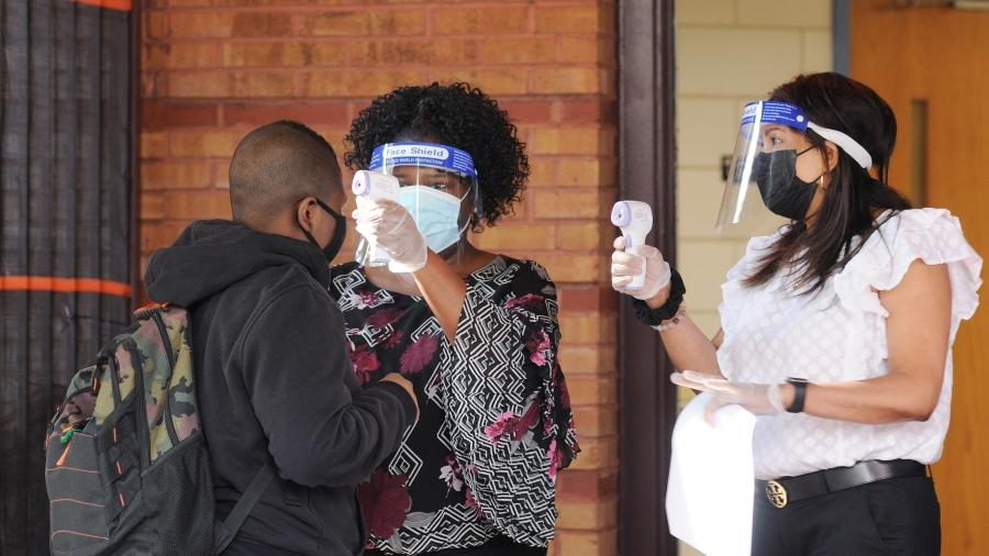 Members of the Building Response Team, including speech teacher Judith Wynter (center), perform temperature checks as students arrive on Sept. 21 for the first day of in-school learning at PS 188 in the Belmont section of the Bronx.
