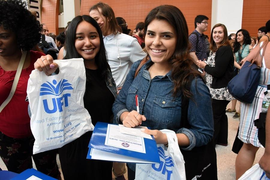 Two women smiling, holding up UFT bag