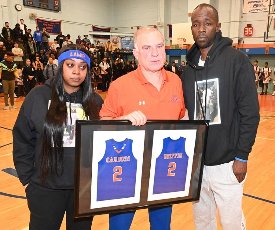 Cardozo HS varsity basketball coach Ron Naclerio (center) presents Aamir Griffin's mom, Shanequa Griffin, and father, Warren Wells, with a plaque showing Aamir's Cardozo jersey.