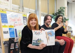 Actor Annie Golden (left) reads a book written by playwright David Caudle (middl